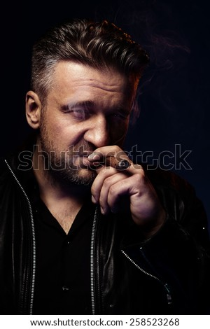 Portrait of a tough guy smoking cigar - stock photo