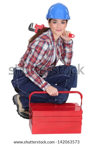 Portrait of a tradeswoman with a pipe wrench and a toolbox