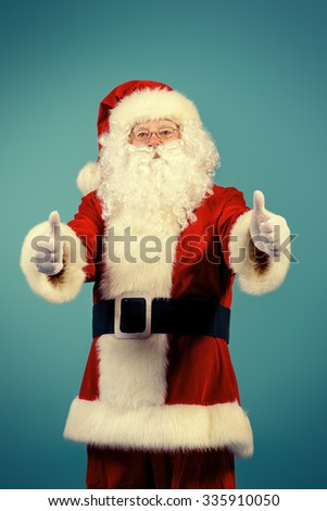 Portrait of a traditional Santa Claus showing thumbs over blue background. Studio shot. Christmas. - stock photo
