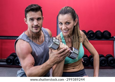 Portrait of a trainer supervising a woman lifting dumbbells - stock photo