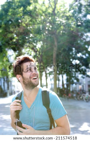 Portrait of a traveling man smiling with bag and cellphone - stock photo