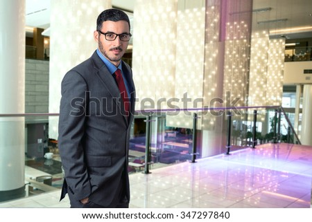 Portrait of a traveling successful corporate business man executive in a hotel lobby workplace confident stylish CEO - stock photo