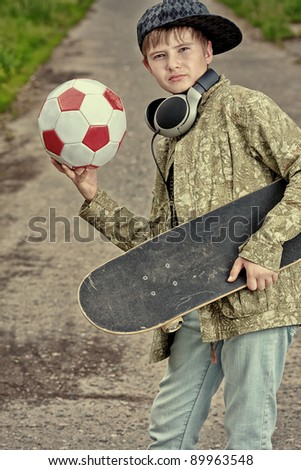 Portrait of a trendy boy teenager with skateboard and ball outdoors. - stock photo