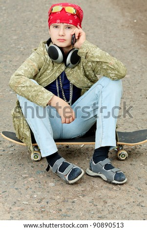 Portrait of a trendy boy teenager with skateboard outdoors. - stock photo