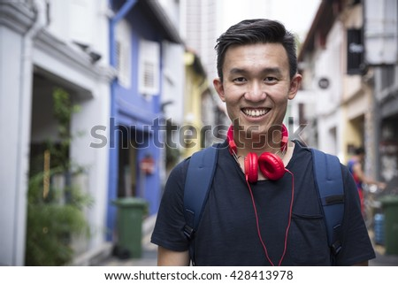 Portrait of a trendy Chinese man lstanding in an urban street.