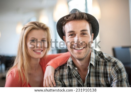 portrait of a trendy couple in a cafe, man wears a hat - stock photo