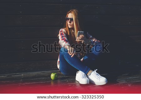 Portrait of a trendy funky women chatting on her cell telephone during recreation time in summer day, young fashionable female waiting for a call on mobile phone while sitting alone outdoors  - stock photo