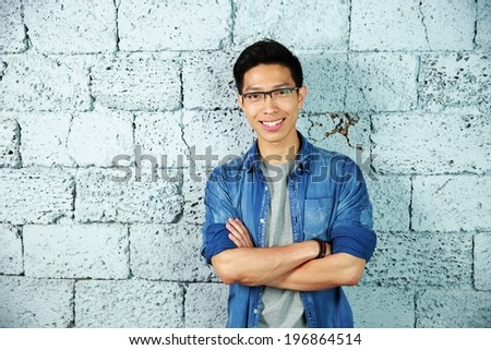 Portrait of a trendy smiling asian man leaning on brick wall - stock photo