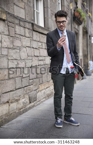 Portrait of a trendy urban man using his Smart Phone and holding a skateboard. - stock photo
