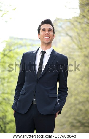 Portrait of a trendy young businessman smiling outdoors - stock photo