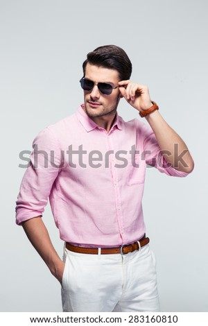 Portrait of a trendy young man in sunglasses and pink shirt over gray background - stock photo