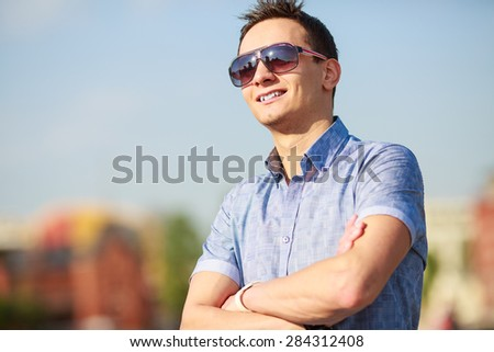 portrait of a trendy young man in the city - stock photo