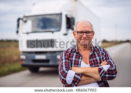 Portrait of a truck driver with crossed arms standing in front of the truck.