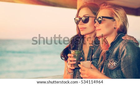 Portrait of a two beautiful girls spending leisure time in the outdoor cafe, drinking tasty cocktails and enjoying beautiful sea view in bright sunny day