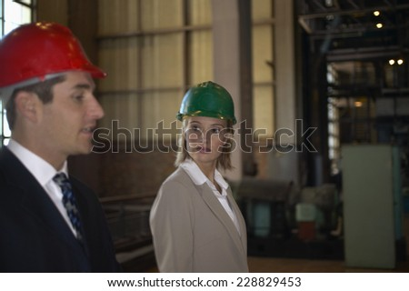 Portrait of a two business people in a hard hats in a factory setting