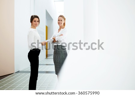 Portrait of a two female colleagues at work standing with digital tablet  in modern interior, young confident women office worker posing with touch pad while met during break in hallway of big company - stock photo