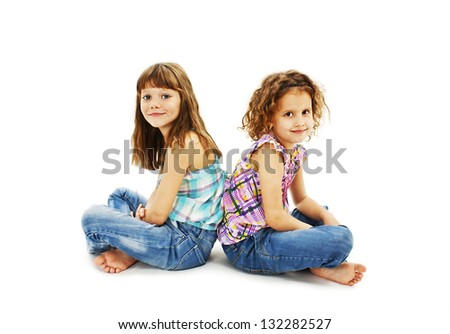 Portrait of a two little girls sitting back to back and smiling. Isolated on white background