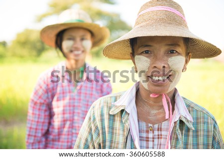 Portrait of a two Myanmar female farmers with thanaka powdered face at farmland.