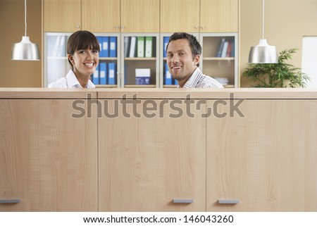 Portrait of a two smiling office workers behind cubicle - stock photo