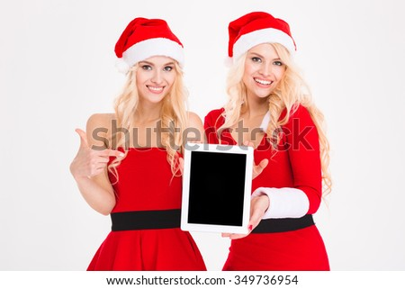 Portrait of a two smiling women in santa cloth showing tablet computer screen isolated on a white background - stock photo