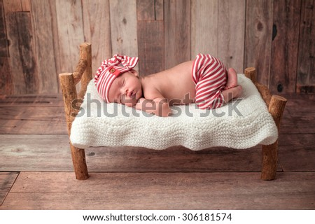 Portrait of a two week old newborn baby boy. He is sleeping on a miniature bed wearing red and white striped pajamas. Shot in the studio on a rustic wood background. - stock photo