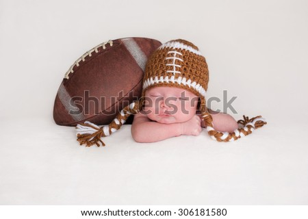 Portrait of a two week old, sleeping newborn baby boy. He is posed with an American football wearing a crocheted football hat. - stock photo
