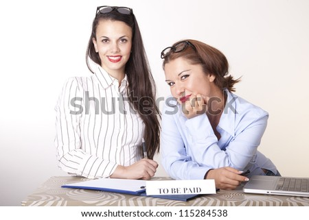 Portrait of a two young beautiful female receptionists with a sign. - stock photo