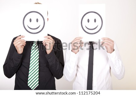 Portrait of a two young men holding smiley faces.