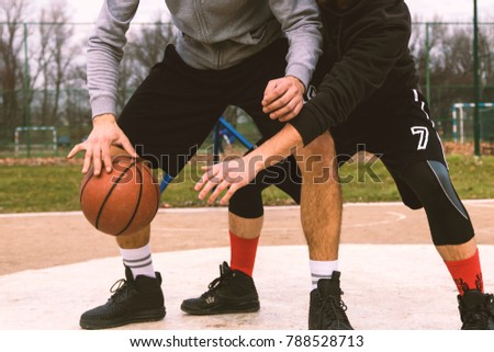 Portrait of a two young sports men playing basketball at the playground. summer vacation, sport, games and friendship concept.