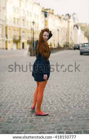 Portrait of a Ukrainian ginger woman in front of a green wall with green eyes, dark blue dress and orange pantyhose.