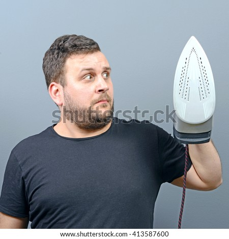 Portrait of a unhappy and confused man holding iron - stock photo