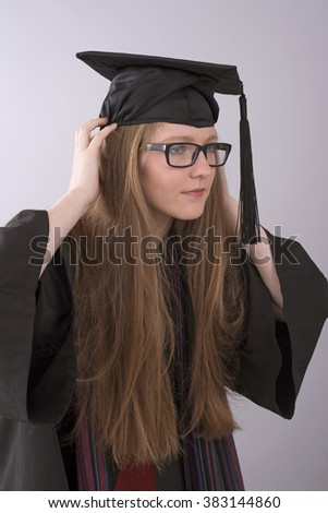 Portrait of a university student adjusting her graduation cap
