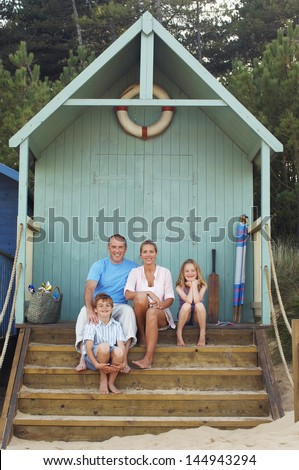 Portrait of a vacationing Family sitting together in beach hut - stock photo