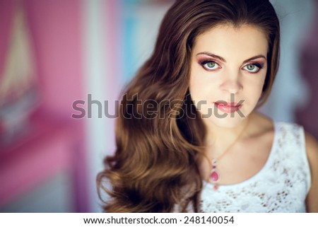 Portrait of a very beautiful girl with big eyes and gorgeous hair in a white dress - stock photo