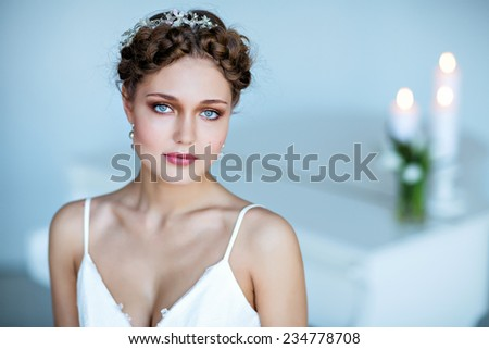 Portrait of a very beautiful sensual girl with braids and blue eyes in a white dress - stock photo