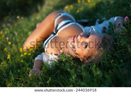 Portrait of a very beautiful woman laying in grass in lingerie in summer - stock photo