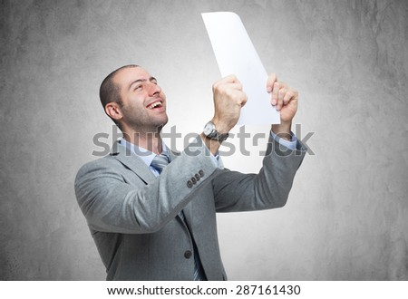 Portrait of a very happy man holding a document - stock photo