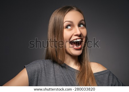 Portrait of a very happy woman laughing and looking aside. Isolated over grey background. - stock photo
