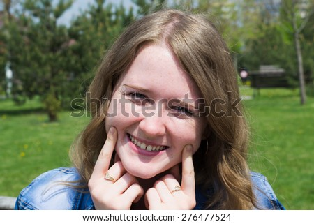 portrait of a very happy young girl who is smiling and holding his fingers on the cheeks - stock photo