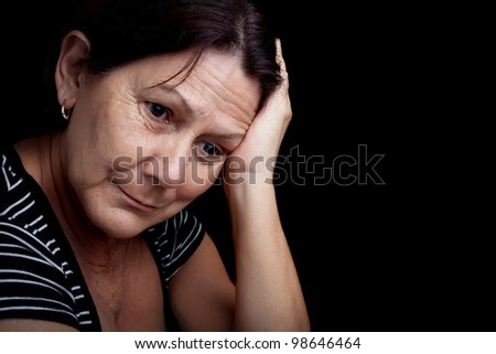 Portrait of a very sad and depressed older woman suffering from stress or a strong headache isolated on black - stock photo