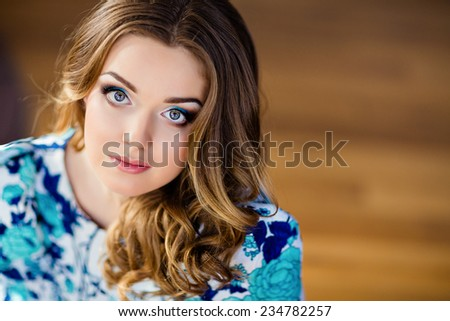 Portrait of a very sexy beautiful girl with blue eyes in a blue dress