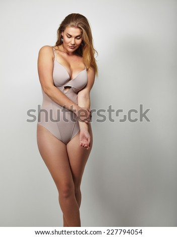 Portrait of a voluptuous woman in lingerie looking down on grey background. Attractive plus size young lady in body stocking. - stock photo