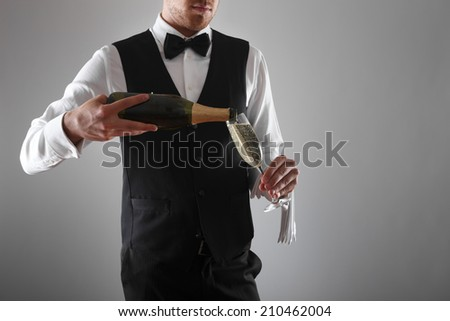 Portrait of a waiter holding a champagne bottle - stock photo