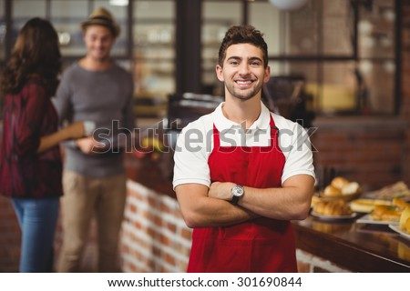 Portrait of a waiter with arms crossed at the coffee shop - stock photo