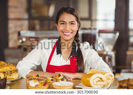 Portrait of a waitress standing over pastries at the coffee shop - stock photo