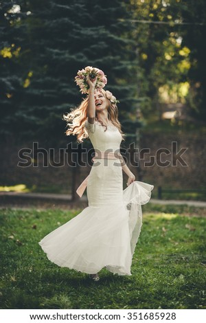 Portrait of a wedding bride posing in a white hipster style dress with flowers in her hands in the forest on sunset - stock photo