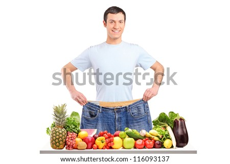 Portrait of a weight loss male showing his old jeans isolated on white