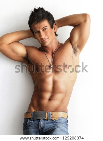 Portrait of a well built shirtless muscular male model against white background