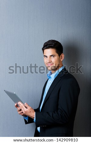 Portrait of a well dressed businessman holding a tablet computer and looking at camera, isolated on blue background. - stock photo