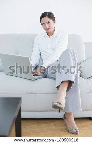 Portrait of a well dressed young woman using laptop on sofa at home